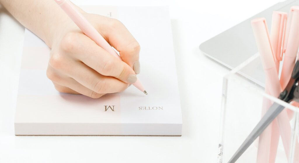 Image of a woman's hand handwriting some notes